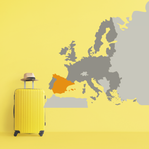 Yellow suitcase beside image of a map of Europe on yellow wall